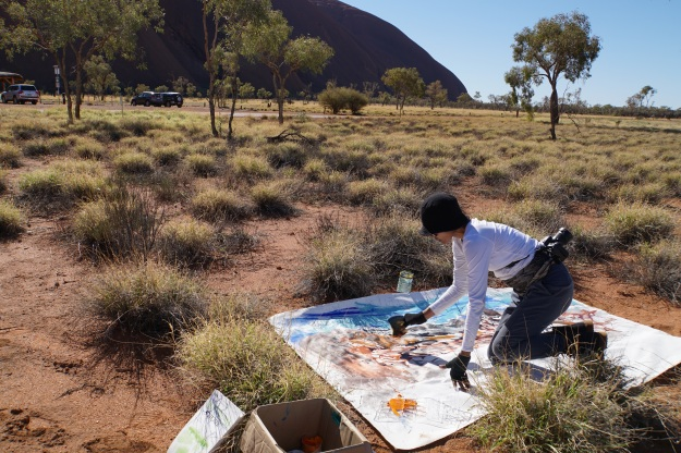 Artist Ni Nyoman Sani painting on location at Uluru. Image Made Budhiana