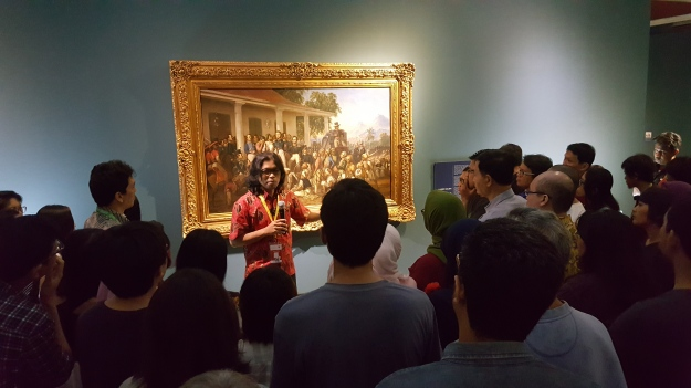 1771-curator-mikke-susanto-explaining-the-significance-of-the-painting-by-raden-saleh-penangkapan-pangeran-diponegoro-1857-during-the-curators-exhibition-tour-image-richard-horstman