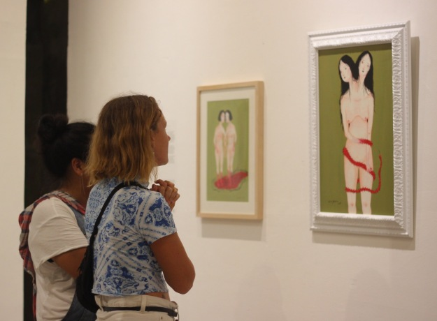 "Members of the public engage with paintings by Citra Sasmita during the opening of ""Tanda Seru"" at Uma Seminyak - Image courtesy of Futuwonder"