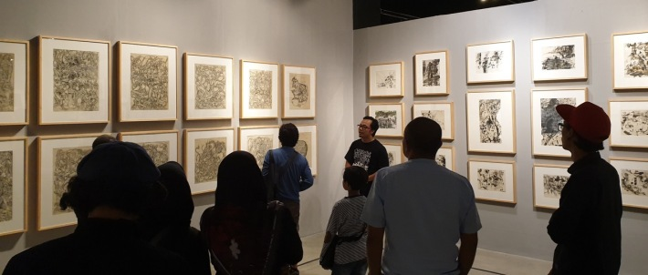 Exhibition co-curator Gede Arya Sucitra discussing Sukari's pen on canvas compositions - Image Richard Horstman
