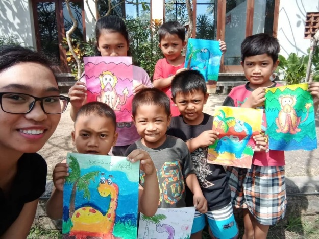 Volunteer art teacher Mega with local children and the outcome of one of her weekly art workshops.