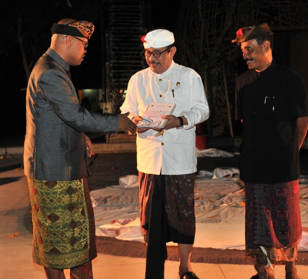 During the opening ceremony of Bali Megarupa 10 October 2019 at ARMA, Dr Wayan Kun Adnyana presents the Bali Megarupa exhibition catalog to Bali Deputy Governor Cokorda Ace as ARMA founder Agung Rai looks on. Image coutesy of Bali Megarupa.
